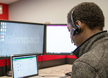 A member of Impact's IT careers team talks to a customer via a headset