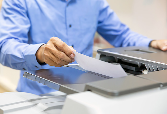 man pulling out paper from a printer