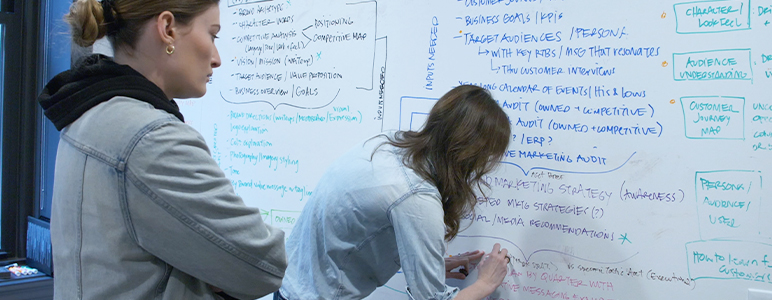 two female coworkers writing on a white board